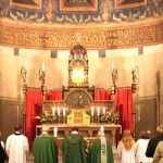 Photo of priests facing altar vested in green, with congregation and servers.
